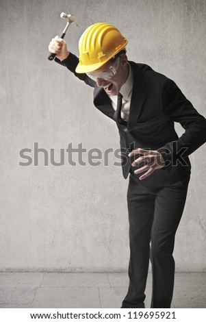 Young businessman, wearing a bob, breaking something with a gavel