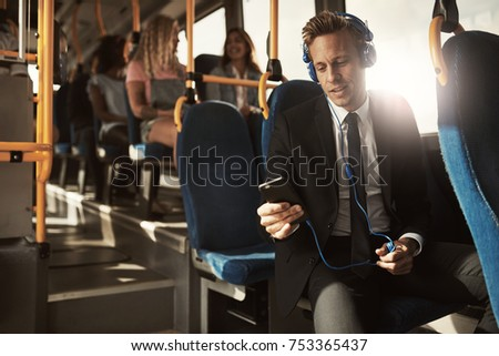 Young businessman wearing a suit smiling while sitting on a bus during his morning commute listening to music on a smartphone and headphones