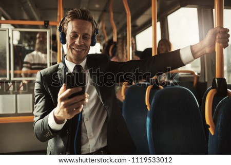 Young businessman wearing a suit standing on a bus during his morning commute listening to music on a smartphone and headphones