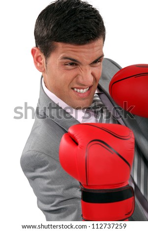 young businessman wearing boxing gloves