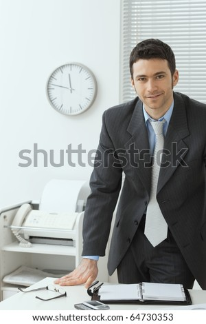 Young businessman wearing grey suit, standing behind office desk, smiling.?