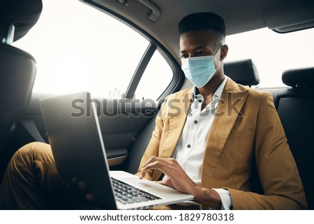 Young Businessman Wearing Mask Working On Laptop In Back Of Taxi During Health Pandemic Сток-фото ©