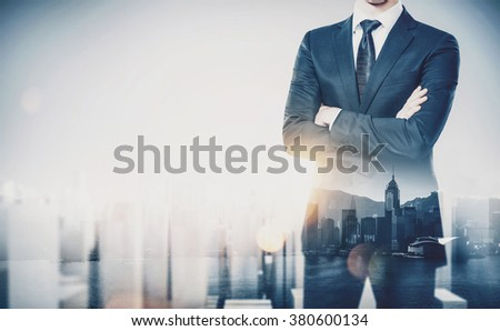 Young businessman wearing modern suit and standing with his arms crossed. Double exposure. Horizontal, contemporary city background
