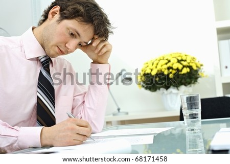 Young businessman wearing pink shirt, sitting at office desk and writing on paper, leaning on hand, thinking.