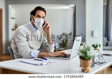 Young businessman wearing protective face mask while working on laptop and talking on mobile phone at home office.