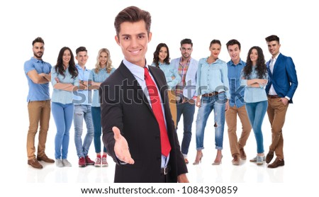 young businessman welcomes you to his casual team with a handshake while standing on white background #1084390859
