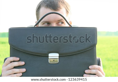 Young businessman who is afraid of anything and covering his face of the business briefcase  on  sky and green grass field