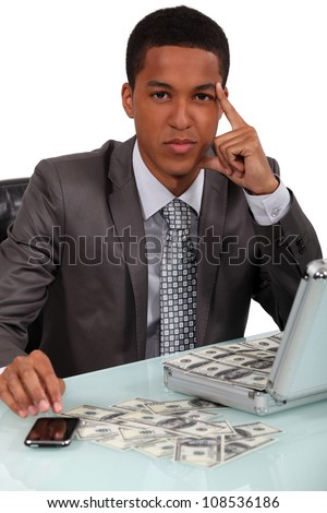 Young businessman with a briefcase full of money