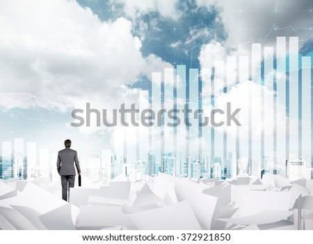 young businessman with a case standing on sheets of paper scattered on the ground and looking in front. New York, sky with clouds and a bar chart at the background. Concept of future #372921850