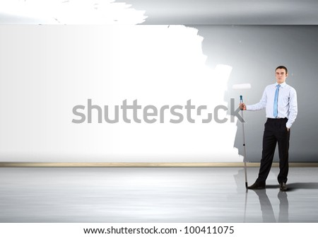 Young businessman with a paint brush against blank white wall