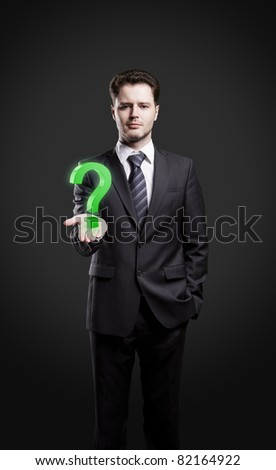 Young  businessman with a question mark on his hand. Isolated on a black background
