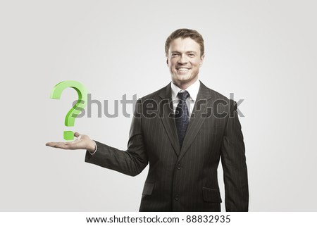 Young  businessman with a question mark on his hand.On a gray background