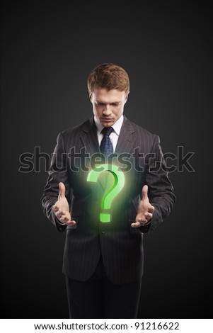 Young  businessman with a question mark on his hands. On a black background