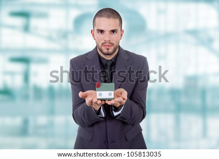young businessman with a small house in his hand