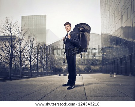 Young businessman with a travel backpack in a city