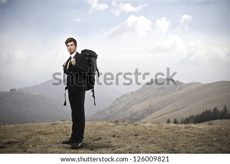 Young businessman with a travel backpack standing on a hill