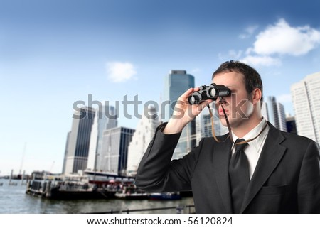 Young businessman with binoculars with cityscape on the background