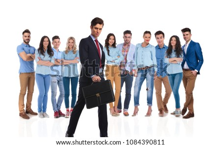 young businessman with briefcase walking in front of his young team on white background while they are standing #1084390811