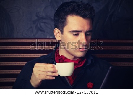 Young businessman with cup of coffee looking at tablet - retro colors