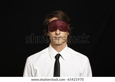 young businessman with eyes covered by sleep mask