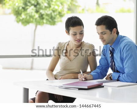 Young businessman with female colleague going over document information at office desk