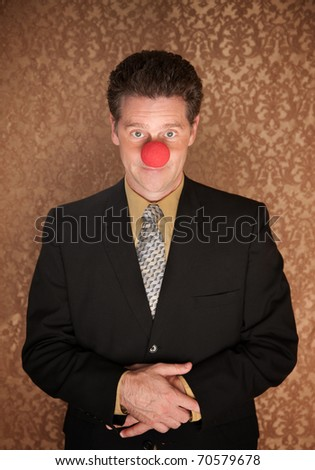 Young businessman with folded clasped hands and clown nose