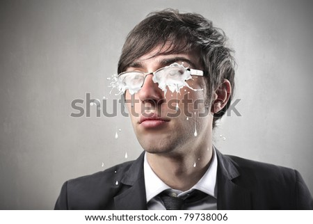 Young businessman with glasses covered with milk