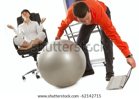 Young businessman with grey ball, looking on laptop screen. His colleague, doing yoga on the office chair
