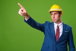 Young businessman with hardhat against green background
