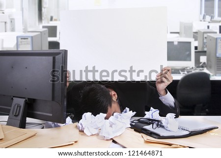 Young businessman with his face down while holding a white copy space at his office