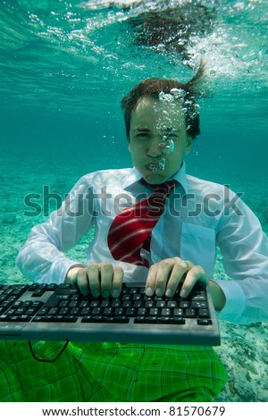 Young businessman with keyboard in formal clothes working underwater - stock photo