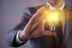 Young businessman with light bulb in idea concept