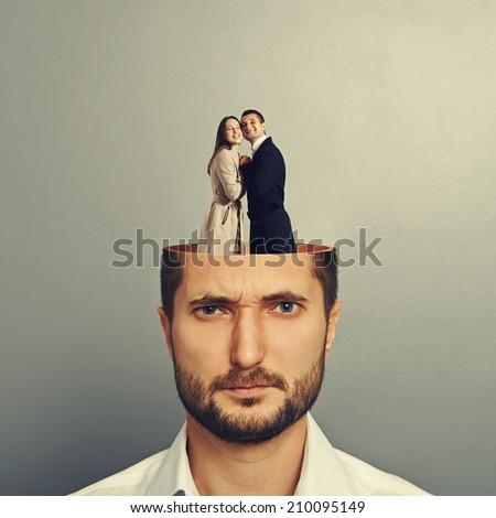 young businessman with open head. couple in love embracing and standing in the man\'s head. photo over grey background