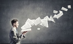 Young businessman with opened book in hands and pages flying in air