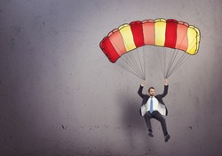 Young businessman with parachute