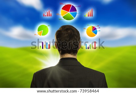 Young businessman with pie charts floating around his head - stock photo