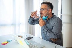 Young businessman with protection mask drinking water while working on laptop in the office. Creative man at work drinking water. Man wearing medical protective mask to protect from virus Covid19