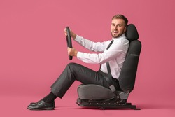Young businessman with steering wheel sitting on car seat against color background