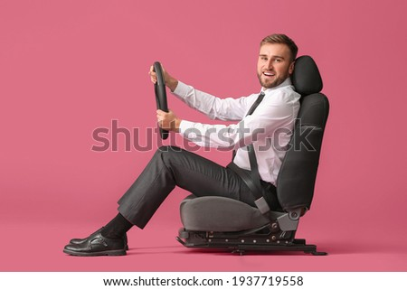 Young businessman with steering wheel sitting on car seat against color background Foto stock ©
