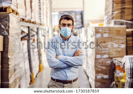 Young businessman with sterile protective mask on standing in warehouse with arms crossed. Protection from corona virus/ covid-19.