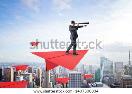 Young businessman with telescope standing on abstract red paper plane on sky and city background. Future and leadership concept  #1407500834