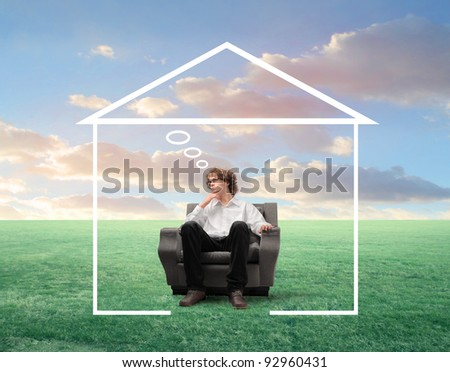 Young businessman with thoughtful expression sitting on an armchair surrounded by the shape of a house