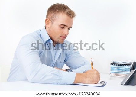 Young businessman working at desk on white background