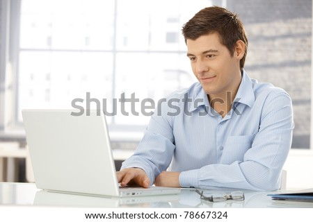 Young businessman working in office, sitting at desk, looking at laptop computer screen, smiling.?