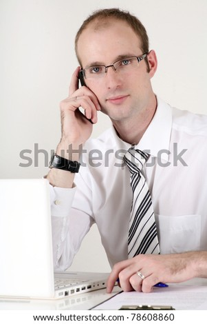Young businessman working on computer and speaking at the phone