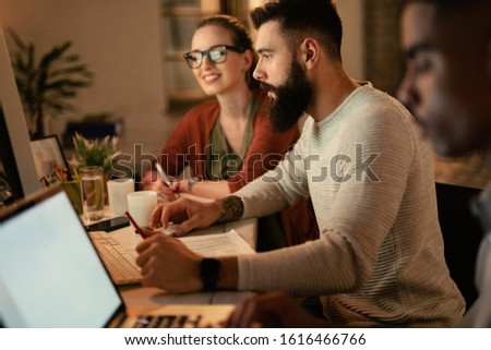 Young businessman working on desktop PC while being with his coworkers in the office.