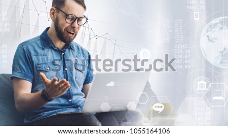 Young businessman working on his laptop full of enthusiasm after getting good news about company income. Finaces, economy, virtual money and crypto currency concept. #1055164106