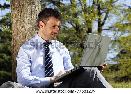 young businessman working on laptop in a park