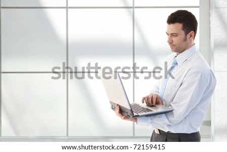 Young businessman working on laptop, standing in office lobby.?