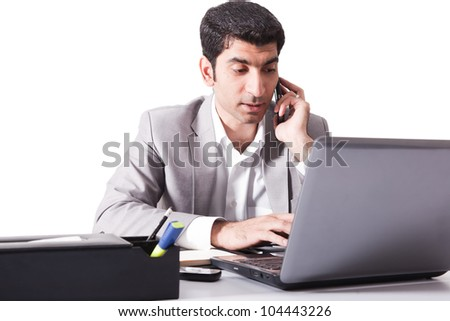 young businessman working on laptop while talking over the cell phone, man multitasking